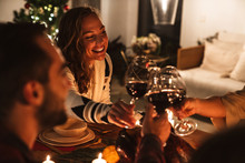 Photo Of People Drinking Wine And Smiling While Having Christmas Dinner