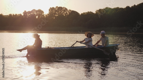 Pinturas sobre lienzo  Young family floating in a boat with oars at sunset