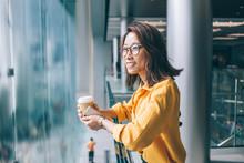 Young Asian Woman With Coffee And Cellphone Leaning On Railing Smiling And Daydreaming