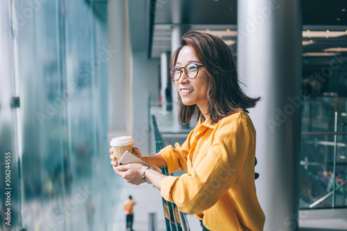 Photo Young Asian woman with coffee and cellphone leaning on railing smiling and daydr