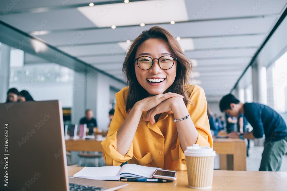 Fototapeta Cheerful female freelancer in workspace