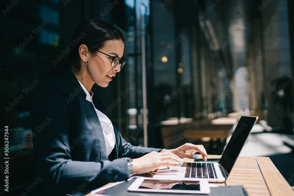 Fototapeta Side view of serious female economist working online with accounting documents on modern laptop device during sunny day in street cafeteria, caucasian businesswoman typing name for media files