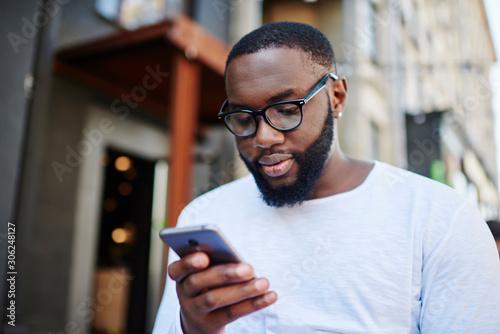 Millennial dark skinned man using smartphone app for booking online while spendi Poster Mural XXL