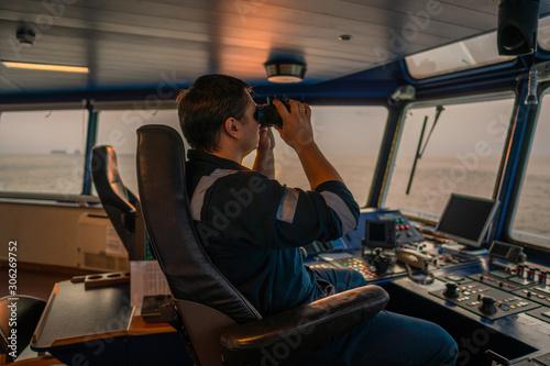 Fotografiet Navigational officer lookout on navigation watch looking through binoculars