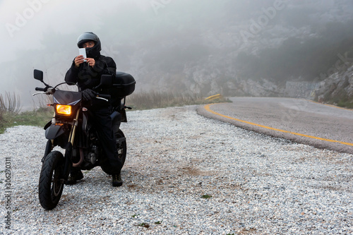 Rider is trying to find signal on his mobile on a foggy day Canvas Print