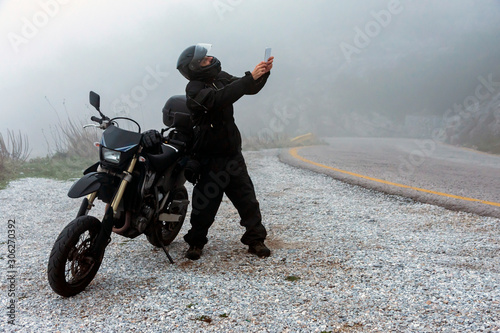 Fotomural Rider is trying to find signal on his mobile on a foggy day