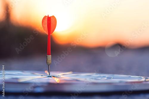 Close up red dart arrow hitting target center dartboard on sunset background Fototapet