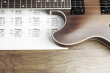 Electric Guitar And Chord Book On A Wooden Texture