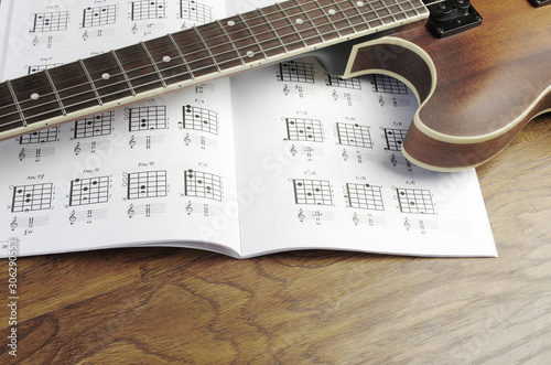 Valokuva Electric guitar and chord book on a wooden texture