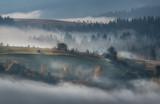 Wspaniały widok na wioskę spowitą mgłą. Rytmiczne wzgórza we mgle. Wcześnie rano Jesienny czas. Stan słoneczny. Mały dom w gęstym lesie. Natura niebieskie tło. Karpaty. Zachodnia Ukraina - 306298776