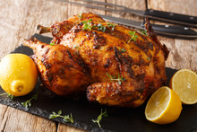 Tasty Aromatic Rotisserie Chicken With Thyme, Lemon And Spices Close-up On A Slate Board. Horizontal