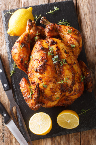 Fototapeta Freshly cooked rotisserie chicken with ginger and spices close-up on a slate board. Vertical top view obraz