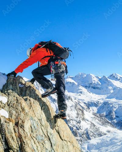Alpinist klettert gewandt im Hochgebirge Wallpaper Mural