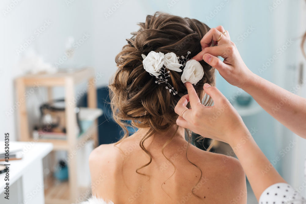 Fototapeta hairdresser makes an elegant hairstyle styling bride with white flowers in her hair