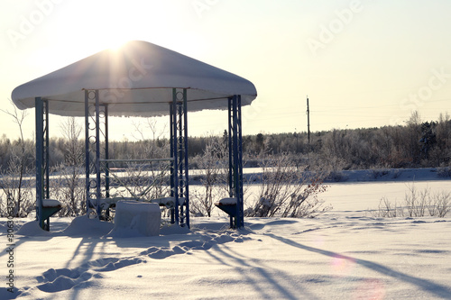 Photo Gazebo, covered with snow on the background of the winter landscape in the rays of the setting sun