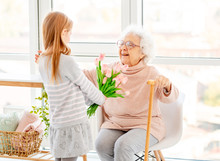 Girl Presenting Bouquet To Old...