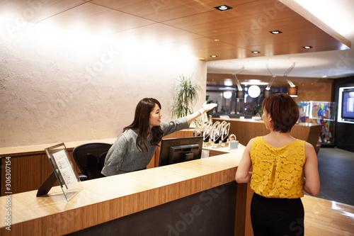 Fototapeta カウンターで来訪者の案内をする女性