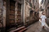 Fototapeta Uliczki - islamic man walking through narrow streets of Stonetown