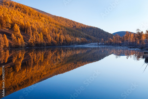 Fotomural  Mountain lake with autumn trees and its reflection in the water