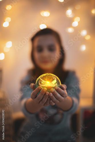 Niña en navidad con bola mágica y luces por las fiestas de la natividad Canvas Print