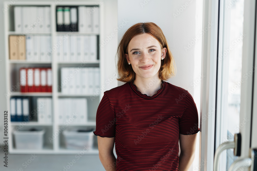 Fototapeta Smiling businesswoman standing at the office door