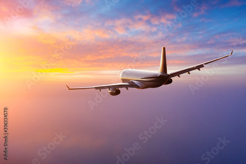 Fényképezés  Passengers commercial airplane flying above clouds in sunset light