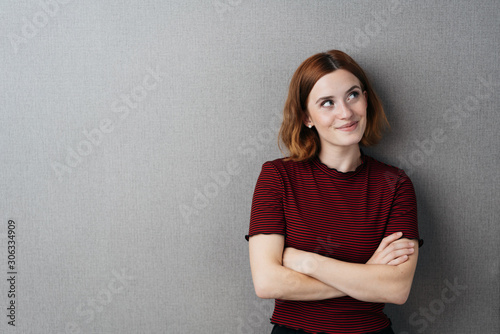 Fotomural Pretty young woman standing thinking with a smile