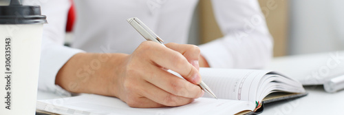 Female hand holding silver pen ready to make note in Fototapet
