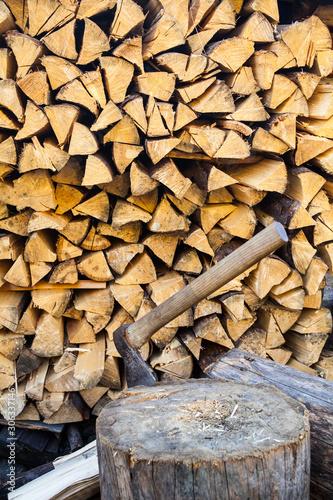 Fotografija Axe in a stump near the stack of firewood