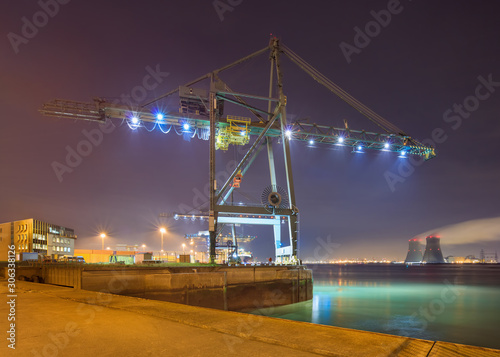 Cuadros en Lienzo Night scene with view on with illuminated container terminal and massive crane, Port of Antwerp, Belgium