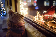 Little Boy Admires Christmas Decorations In Showcase Of Shop On Winter Evening. Tourist Looking On Xmas Toys And Accessories On Traditional Christmas Market In Tallinn.