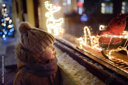 Little boy admires Christmas decorations in showcase of shop on winter evening Canvas Print