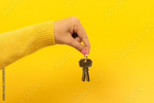 Cuadros en Lienzo female hand holding house keys, suggesting, over yellow background