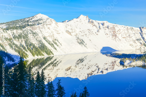 Green pine tree lush and reflection of snowcap mountain with Wizard Island on Crater Lake