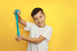 canvas print picture - a cheerful boy with dark hair in a white t shirt on a yellow background stretches a blue slime in his hands