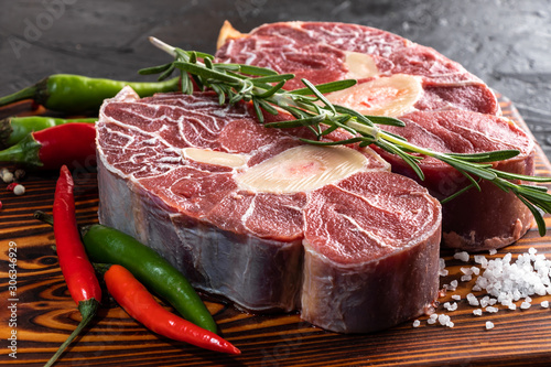 Obraz Meat beef veal shank sliced meat on dark  wooden cutting board. - fototapety do salonu