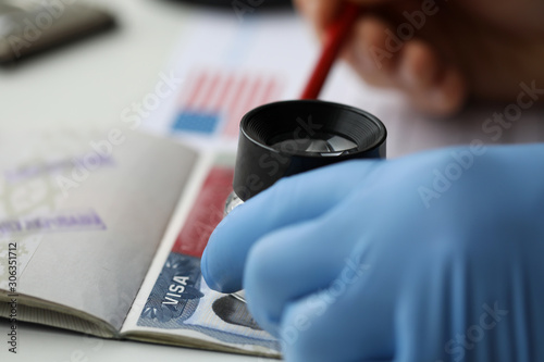 Specialist with loupe checking authenticity of american visa in passport Fototapeta