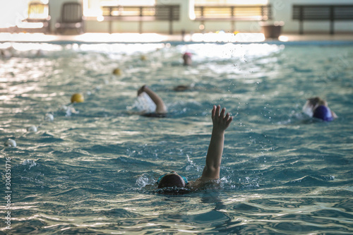 An unknown person is swimming a backstroke style in a pool Wallpaper Mural