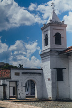 White Clock Tower Of La Merced Church, Next To Museo Del Arte Religioso Or The Museum Of Religious Art In Cali, Colombia. Sunny Weather With Some Clouds