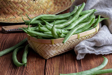 Fresh And Raw Green Beans (green Round Beans) In Wicker Basket. Rustic And Homemade Look On Wooden Background.