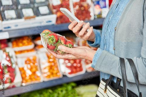Photo Kundin scannt Packung Erdbeeren mit Smartphone