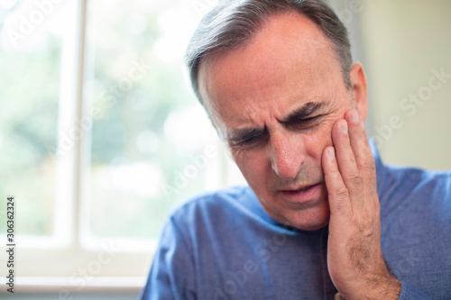 Fotomural  Mature Man Suffering With Toothache And Rubbing Painful Tooth