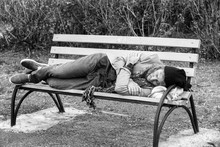 Black And White Portrait Of Poor Homeless Man Sleeping On Bench Outdoors
