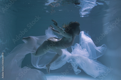 Papiers peints Cygne Beautiful girl gymnast and sportswoman swims underwater with shining fabric in the pool