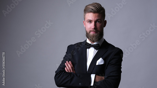 Foto Handsome caucasian man with beard in classic black suit.