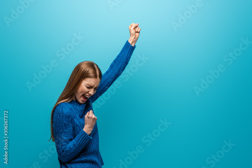 Obraz na plátně beautiful cheerful woman in blue knitted sweater celebrating triumph, isolated o