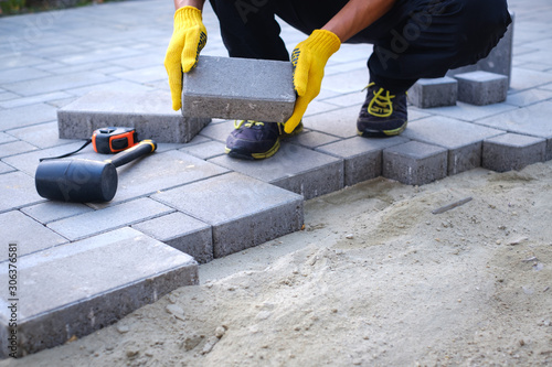 Photo The master in yellow gloves lays paving stones