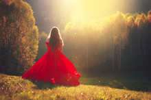 Beautiful Young Girl In A Red Dress In Fantastic Autumn Nature. Fashion Photo