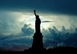 Silhouette of Statue of Liberty over dramatic skies, New York, USA