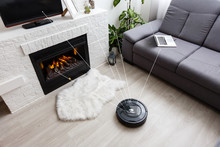 Robotic Vacuum Cleaner On Laminate Wood Floor Smart Cleaning Technology.